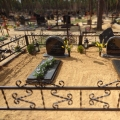 Kapavietas noformējums ar kaltiem pieminekļiem un pusslēgtiem granīta kapu rāmīšiem