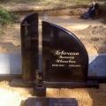 Pulēts melnā granīta piemineklis ar pusslēgtu kapu rāmīti